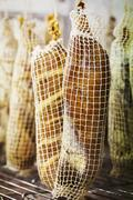 Close up of air dried meat wrapped in nets hanging incharcuterie Stock Photos