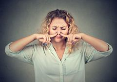 Woman pinches nose with fingers looks with disgust something stinks Stock Photos