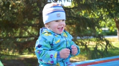 Baby smiling in a Park sitting on the bench Stock Footage