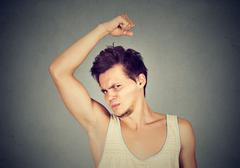 Man, smelling, sniffing his armpit, something stinks bad, foul odor Stock Photos