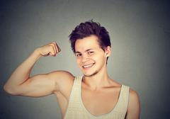 Fit and muscular young man flexing his biceps Stock Photos