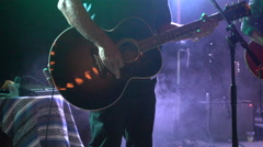 A musician plays a guitar on stage. Stock Footage