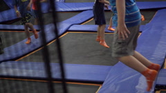 A boy jumps on a trampoline while playing dodge ball. Stock Footage