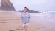 Attractive active senior woman walking along the ocean surf. Stock Footage