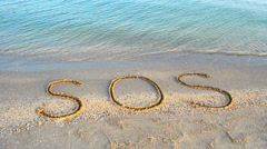 The inscription SOS on sand Stock Footage