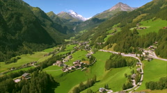 Green pastures in scenic alpine valley Heiligenblut in the Alps, aerial footage Stock Footage