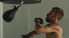 Young athlete working out by throwing punches at a punching bag Stock Footage