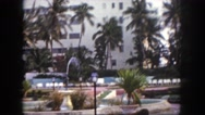 1960: outdoor of resort with fountain and chairs with palm trees FLORIDA Stock Footage