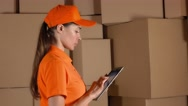 Girl in orange uniform counting storage boxes and using her tablet against brown Stock Footage