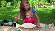 Painter mother with her toddler daughter girl paint wooden fish decoration Stock Footage