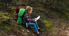 Child girl 8-9 years hiker on a halt looking at topographic map in forest Stock Footage