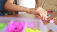 Little girl weave wristband of rubber bands. Colored rubber bands for weaving Stock Footage