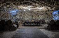 An old wine cellar with oak barrels full of red wine Stock Photos