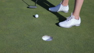 The golfer uses puts the ball in the hole. Close Up. Stock Footage