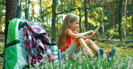 Hiker girl child 8-9 years using smartphone and sitting in the grass in forest Stock Footage