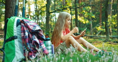 Hiker girl child 8-9 years using smartphone and laughing sitting in the grass Stock Footage