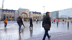 Citizens walk across square against Helsinki Central Railway Station at morning Stock Footage