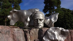Jean Sibelius Monument in Helsinki. Shining face bas-relief on granite pedestal. Stock Footage