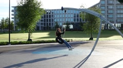 Young woman happily swing on tire at empty morning park Stock Footage