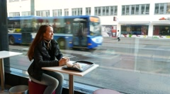 Young woman in bistro at early morning, sit against large window, drink coffee Stock Footage