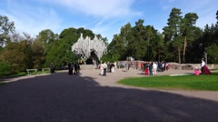 Groups of Asian tourists stand around monument to finnish composer Jean Sibelius Stock Footage
