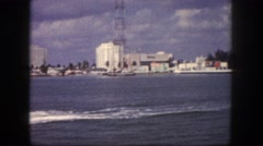 1960: panoramic view of an ocean resort with long bridge and tourist boat Stock Footage