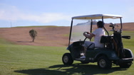 The female golfer uses a golf car on a golf course. Stock Footage