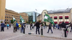 Party activists of Nordic Resistance Movement stand with green flags on square Stock Footage