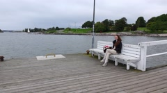 Young woman sit alone on empty ferry landing stage, enjoy view of cold gray sea Stock Footage
