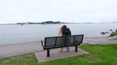 Young woman rest on bench at gulf shore, feel cold and put on hipster hat Stock Footage