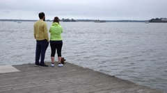 Unidentified couple stand on windy pier corner, look to empty water Stock Footage