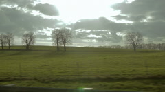 View from passing by car. Green fields and bare trees. Stock Footage
