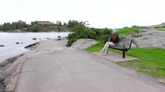 Lonely young woman sit resting on bench at stony shore, fresh breezy place Stock Footage