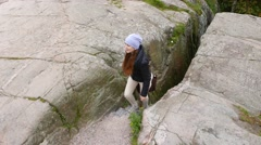 Young woman go upstairs on narrow footpath in rock crack, stony landscape Stock Footage