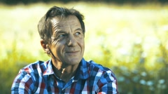 Senior man in checked shirt on sunny summer meadow Stock Footage
