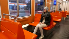 Ordinary tired woman depart from station, sit in empty subway coach Stock Footage