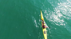 A kayaker paddles in a scenic mountain lake with a drone hovering above him. Stock Footage