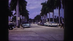 1960: palm tree laden streets car in street intersection everyday paradise life Stock Footage