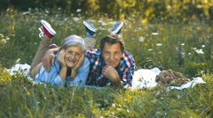 Senior couple in nature lying on a blanket, having picnic Stock Footage