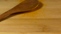 Tumeric being sprinkled with wooden spoon Stock Footage