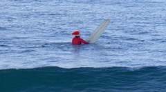 Santa Claus sits on his surfboarding waiting for waves while surfing. Stock Footage