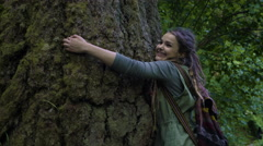Closeup Of Young Woman As She Walks Down Trail And Hugs A Tree, Her Friend Joins Stock Footage