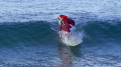 Santa Claus does a hang five trick while riding a wave surfing. Stock Footage