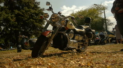 Biker in helmet sits on a motorcycle (chopper) and leaves, autumn weather Stock Footage