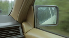 Side-view mirror in a vintage car. Driving along the road, taking turn. Stock Footage