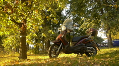 Stylish motorcycle with a windshield standing under a tree in autumn park Stock Footage