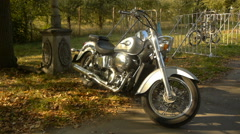 Stylish silver chopper (motorcycle) standing in autumn park, close up Stock Footage