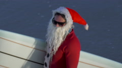 Santa Claus walking with his surfboard to go surfing at the beach. Stock Footage
