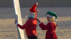 Santa Claus gets help from Mrs. Clause before surfing at the beach. Stock Footage