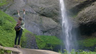 Hiker Runs To End Of Trail, Stops And Raises Her Arms In Front Of Waterfall Stock Footage